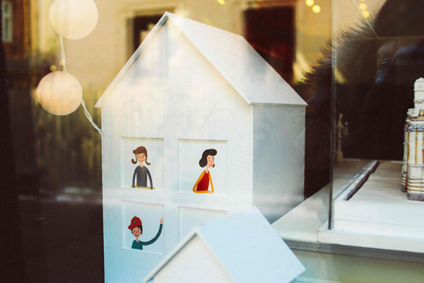 Image of a small wooden house with pictures of people